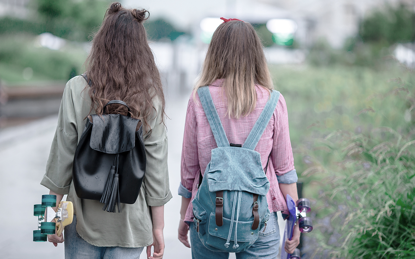 Two teenage girls carrying skateboards